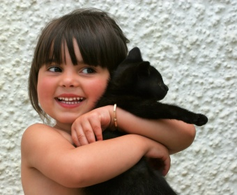 Cliona Schuurman-Smith aged three, holding an all black kitten and smiling.